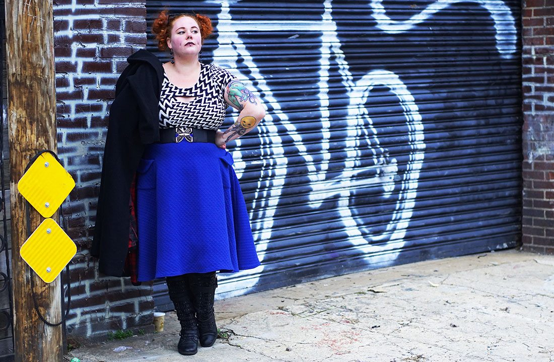 Kobi Jae of Horror Kitsch Bitch talking about her love of Brooklyn, New York City in Torrid Retro Chic Shawl Collar Coat with red tartan lining, Fashion to Figure dress as a top, Tatyana blue quilted circle skirt, and Urbangog knee length riding boots.